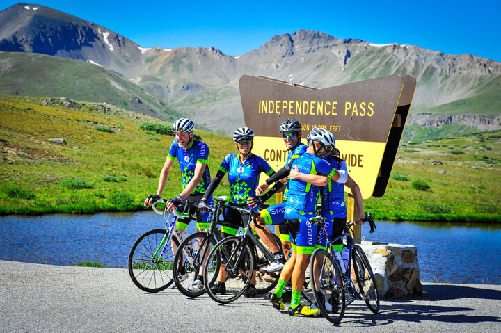 Cyclists in helmets and riding gear in front of Independence Pass sign.